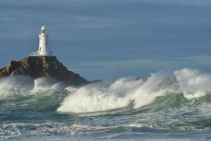 Corbiere lighthouse Jersey UK Autumn waves with a warm sea morning coastal structure image photo