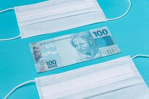 Surgical mask and brazilian real money, on the light blue background photo