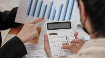 Cerrar empresario y socio utilizando calculadora e informe de puntos para calaulating finanzas, impuestos, contabilidad, estadísticas y concepto de investigación analítica foto