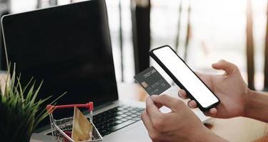 Pago en línea, manos del hombre sosteniendo un teléfono inteligente con tarjeta de crédito para compras en línea. foto