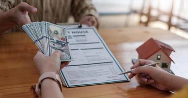 Imagen del agente inmobiliario que ayuda al cliente a firmar el contrato de papel en el escritorio con el modelo de la casa foto
