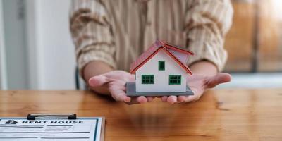 Manos femeninas que salvan la pequeña casa con techo - arquitectura, seguridad, concepto de bienes raíces y propiedad - cerca de las manos protegiendo la casa o el modelo de hogar foto