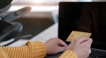Pago en línea, manos del joven usando la computadora y mano que sostiene la tarjeta de crédito para compras en línea foto