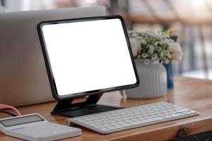 Ordenador portátil de pantalla en blanco y fondo del espacio de trabajo del cartel en la oficina moderna foto