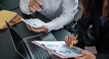 Cerrar empresario y socio con calculadora y computadora portátil para calaulating finanzas, impuestos, contabilidad, estadísticas y concepto de investigación analítica foto