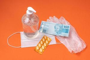 Alcohol gel container, surgical mask, medicine and brazilian real money, on the orange background photo