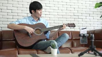jeune homme asiatique jouant de la guitare et chantant à la maison pour une vidéo en direct video