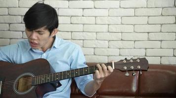 jeune homme asiatique jouant de la guitare et chantant à la maison video