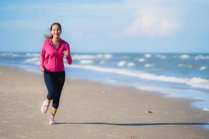 retrato, hermoso, joven, mujer asiática, funcionamiento, y, ejercicio, en, el, tropical, al aire libre, naturaleza, playa, mar, océano foto