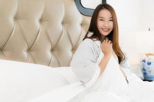 retrato, hermoso, joven, mujer asiática, despertar, feliz, y, sonrisa, en cama, en, dormitorio, interior foto