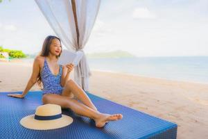 Portrait beautiful young asian woman reading book with happy smile relax in lounge bed chair on the beach sea ocean for leisure photo