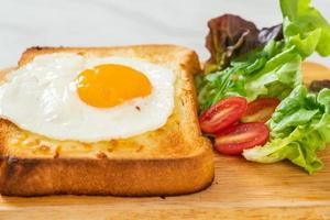 Homemade bread toasted with cheese and fried egg on top with vegetable salad for breakfast photo