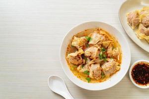 Pork wonton soup or pork dumplings soup with roasted chili - Asian food style photo