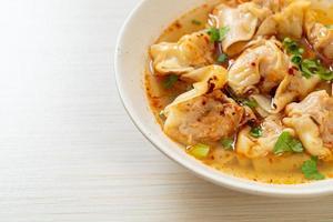 sopa de wonton de cerdo o sopa de albóndigas de cerdo con chile asado - estilo de comida asiática foto