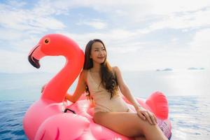 Portrait young asian woman on inflatable float flamingo around outdoor swimming pool in hotel resort photo
