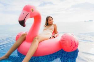 retrato, joven, mujer asiática, en, flotador inflable, flamingo, alrededor, piscina al aire libre, en, hotel, resort foto