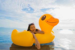 Portrait young asian woman on inflatable float yellow duck around outdoor swimming pool in hotel and resort photo