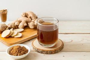 Hot and sweet ginger juice glass with ginger roots - Healthy drink style photo