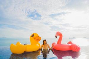 Retrato joven mujer asiática en flotador inflable pato amarillo y flamenco rosado alrededor de la piscina al aire libre en el hotel y resort foto