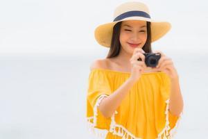 Retrato hermosa mujer asiática usar sombrero con sonrisa feliz ocio en tomar una foto en la playa y el mar en vacaciones de vacaciones