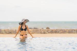 Portrait beautiful young asian woman wear bikini around swimming pool in hotel resort nearly sea ocean beach photo
