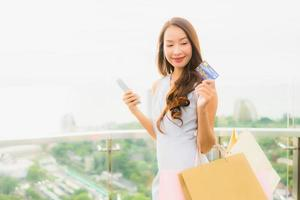 Portrait beautiful young asian woman happy and smile with credit card and mobile or smart phone and shopping bag photo