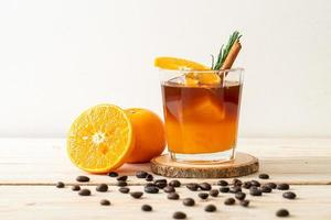 A glass of iced Americano black coffee and a layer of orange and lemon juice decorated with rosemary and cinnamon on a wood background photo