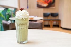 Matcha green tea latte blended with whipped cream and red bean in coffee shop cafe and restaurant photo