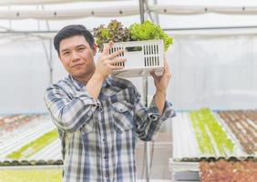 Young farmers hold organic vegetables in the Hydroponics farm. Concept Running a small business photo