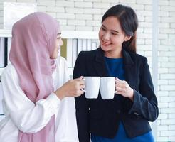 las mujeres musulmanas y las amigas extranjeras hablan y se saludan en la oficina moderna ambas mujeres estaban de pie sosteniendo una taza de café con leche concepto de trabajar profesional y felizmente foto