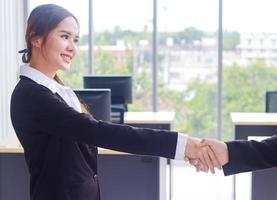 Asian businesswoman smiles and shaking hands after signing a business contract photo