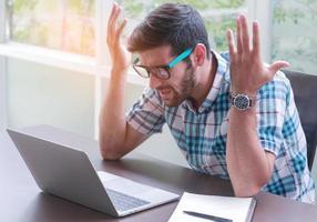 hombre de negocios que trabaja en la computadora portátil con ideas de estrés para trabajar y hacer negocios en línea foto
