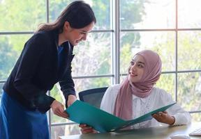 Muslim women and foreign girls working in modern offices Professional and happy working concept photo