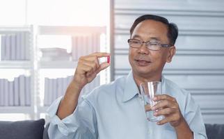 anciano sosteniendo pastillas y cápsulas foto