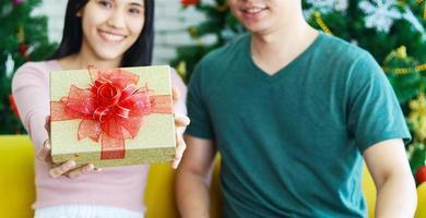 joven pareja asiática está dando un regalo de Navidad. el concepto de una vida feliz en navidad foto