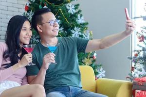 Pareja de jóvenes asiáticos celebran la Navidad felizmente en la casa foto