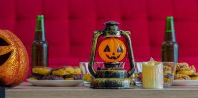 Calabaza naranja en la noche de Halloween con velas y dulces beben en celebración de Halloween foto