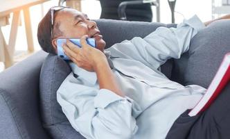 Man talking on the phone Happily on sofa photo