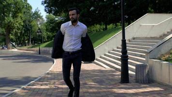 homme d'affaires se promène dans le parc sur la route video