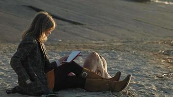une jeune femme sur la plage au bord de la rivière utilise une tablette informatique et nourrit un chien dobro brun au printemps ou en été froid video