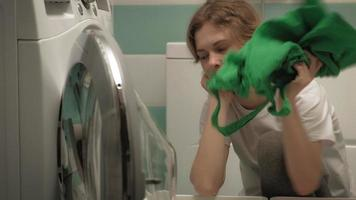 A woman sorts laundry before washing video