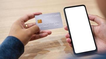 Cerrar la mano de la mujer de compras en línea con tarjeta de crédito mediante un teléfono inteligente en el café foto
