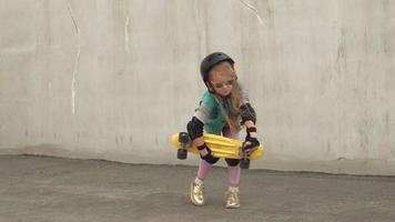 une petite fille joyeuse se tient avec un patin jaune dans les mains et sourit video