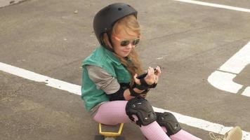 menina alegre está sentada em um skate amarelo e usando um celular, navegando na internet video