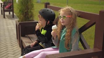 un garçon et une fille sont assis sur un banc de parc et mangent des glaces l'été video