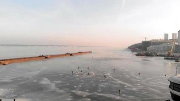 Flying over a frozen river at dawn where people are fishing on the ice video