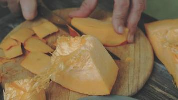 ein Mann schneidet einen orangefarbenen Kürbis video