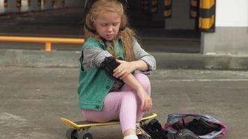 petite fille s'habille casque de protection genouillères et coudières coucher de soleil video