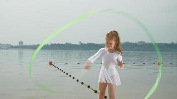 mãe e filha em maiôs brancos, dançando com uma fita de ginástica em uma praia arenosa. amanhecer de verão video