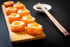 Rollo de sushi de salmón fresco con mayonesa y huevo de camarón - estilo de comida japonesa foto